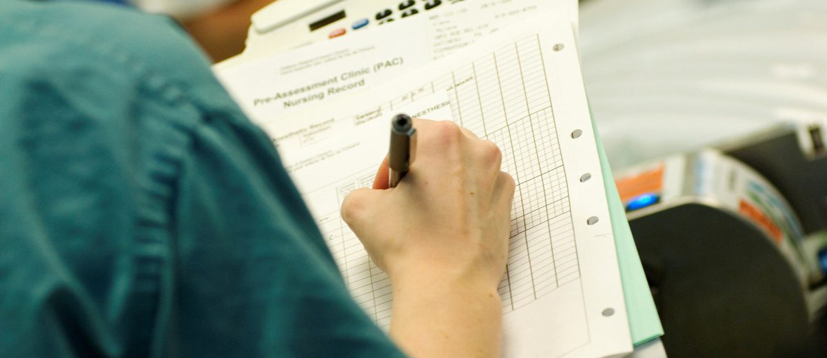 Surgical nurse writing on patient chart.